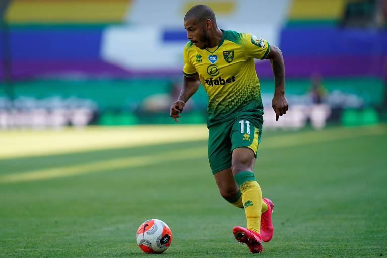 Jogador com uniforme verde-amarelo corre com a bola
