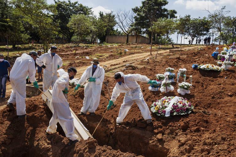 Cinco sepultadores de macacão branco carregam caixão em cova de cemitério.