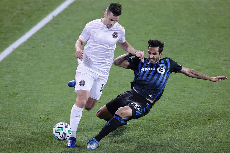 Jogador de azul tenta dar corte em jogador de branco que conduz a bola