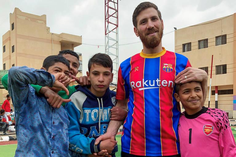 Islam Mohammed Ibrahim Battah, um egípcio com uma notável semelhança com o atacante de Barcelona Lionel Messi, posa para uma fotografia com meninos, na cidade de Zagazig, no Delta do Nilo, ao norte do Cairo, Egito