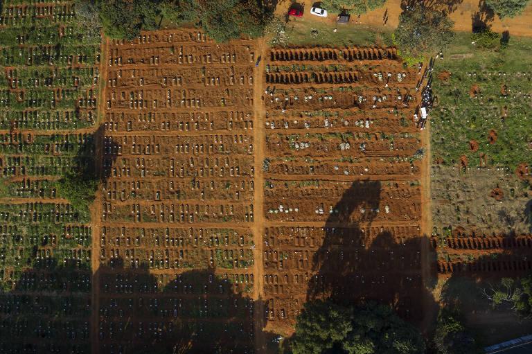 Vista aérea de centenas de túmulos recentes em cemitério ensolarado.