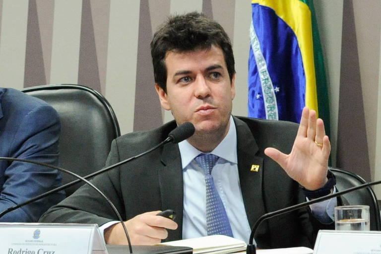 Rodrigo Otávio Moreira da Cruz, cotado para ser o número 2 no Ministério da Saúde, está de terno e camisa branca e gravata. Ele está sentado em uma mesa, com um microfone à frente e gesticulando. Atrás, há uma bandeira do Brasil