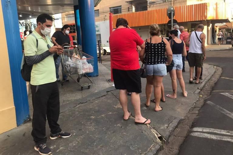 pessoas na fila na frente de mercado