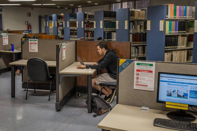 Aluno na biblioteca da FGV em 2018, antes da suspensão das aulas presenciais