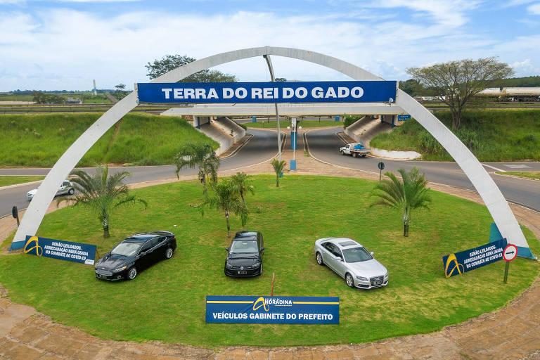"""Imagem aérea mostra três veículos numa rotatória em Andradina, com um monumento com a inscrição """"Terra do Rei do Gado"""""""