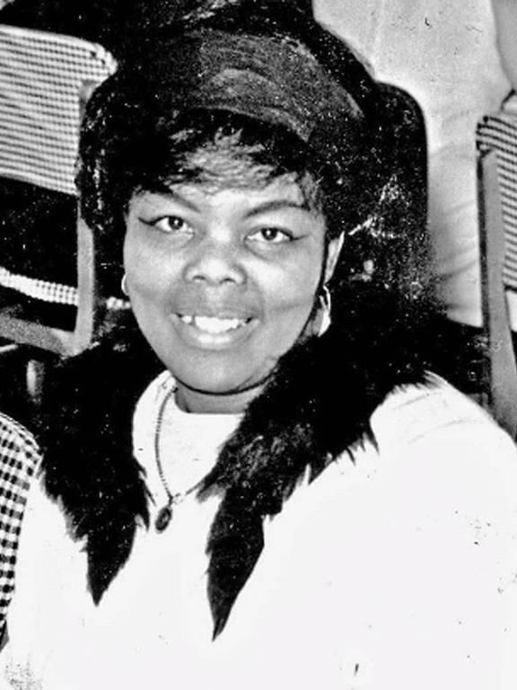 mulher negra de rosto redondo e cabelos curtos com faixa no cabelo em retrato sorridente em preto e branco