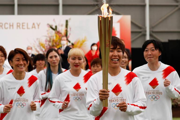 Representantes da seleção feminina de futebol do Japão campeã mundial em 2011 dão início ao revezamento da tocha olímpica em Fukushima; a cerimônia de abertura foi realizada num antigo centro de treinamento do futebol japonês