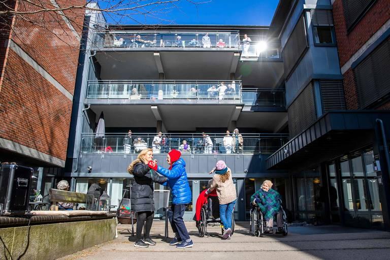 Com abrigos contra o frio, idosos se movimentam em pátio, em dia de céu azul