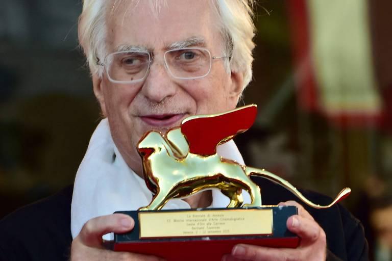 Homem branco idoso e vesgo segura troféu dourado e sorri posando para foto