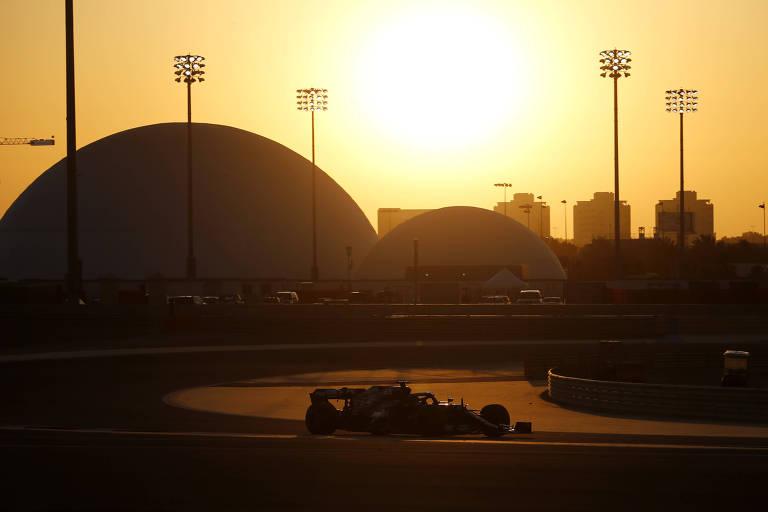 Carro na pista durante pôr do sol, com céu amarelado