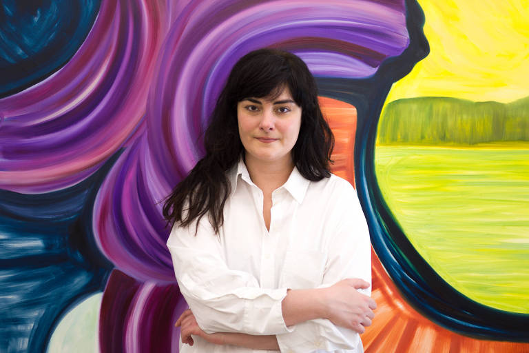 Mulher e cabelos longos pretos e camisa branca, de braços cruzados, posa em frente a tela super coloruda