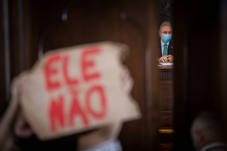 """Cartaz com a inscrição """"Ele não"""" em letras grandes e vermelhas está em primeiro plano, desfocado. Em segundo plano há a fresta de uma porta que mostra o ministro dentro dessa ala, sentado, atrás de uma mesa"""