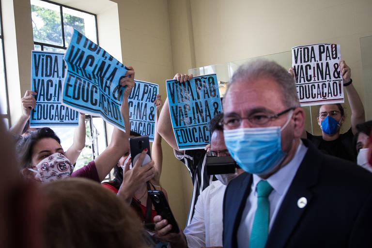 O ministro da Saúde, Marcelo Queiroga, de máscara, circula entre  estudantes. Há aglomeração