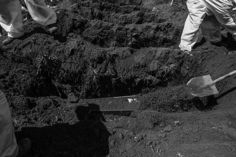 Coveiros jogando terra nas covas