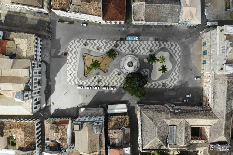 Imagem aérea de pontos turísticos de Salvador sem movimentação de pessoas. Ao centro da imagem, há uma praça com pequenas árvores
