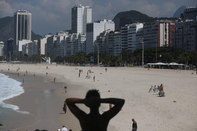 Pessoa de costas coloca os braços na cabeça; ela está contra a luz na foto preto e branco que mostra a praia do Leme em segundo plano