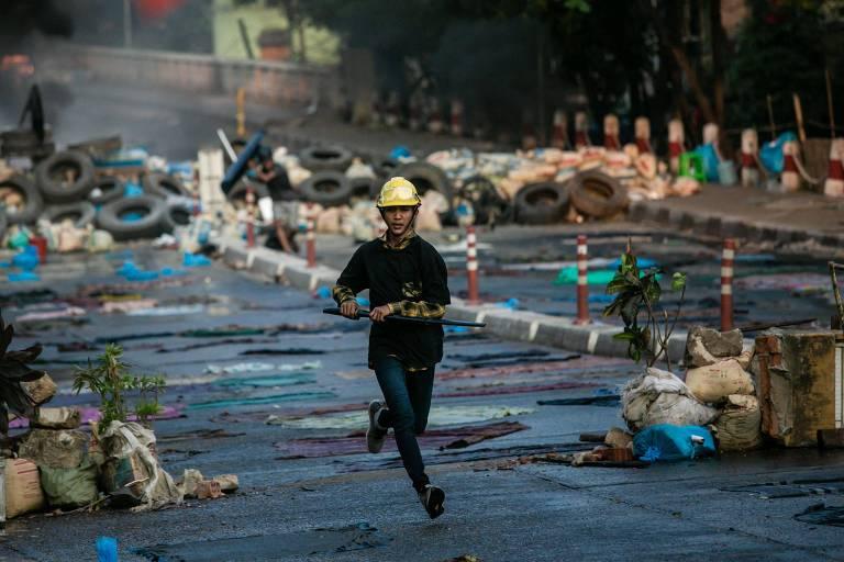 Manifestante em Yangon corre durante protesto contra golpe militar em Mianmar