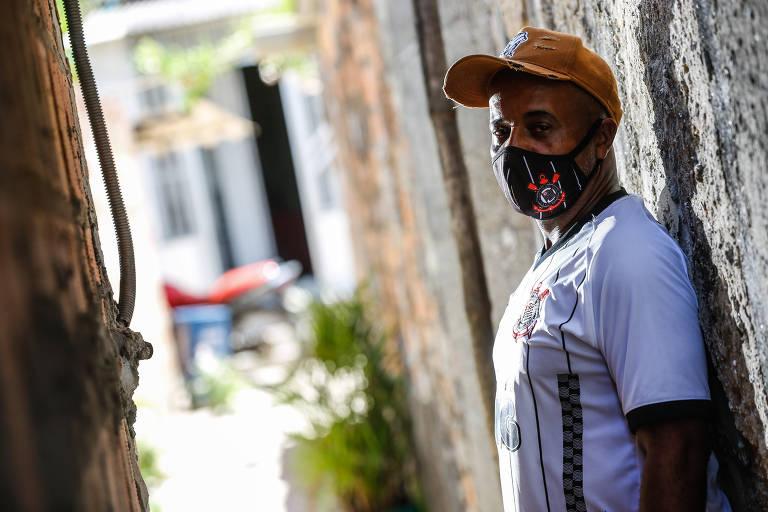 O pescador Carlos Alberto Santana está encostado em uma parede no lado direito da foto. Ele usa boné, máscara e uma camiseta branca estampada