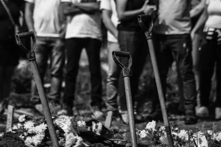 Pessoas em frente a pás que cavaram covas de vítimas de Covid