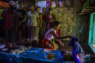 Family members and relatives mourn near the body of Kyaw Htet Aung, 19, a high school student who was shot by security forces, in Dala, Myanmar on March 27, 2021. (The New York Times)