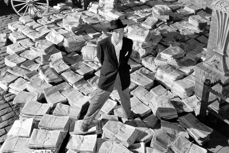 O personagem Charles Foster Kane (Orson Welles) em cima de pilhas do seu jornal, em cena de 'Cidadão Kane' (1941)