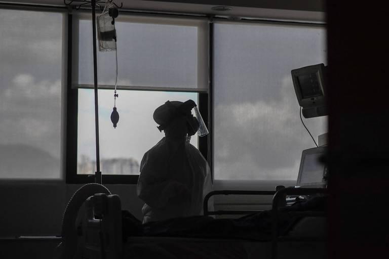 Profissional de saúde próximo a paciente com coronavírus em UTI de centro médico em Caracas
