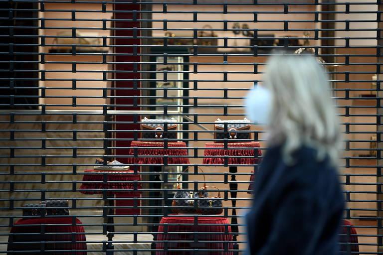 Mulher de máscara caminha em frente a loja fechada em Milão, na Itália