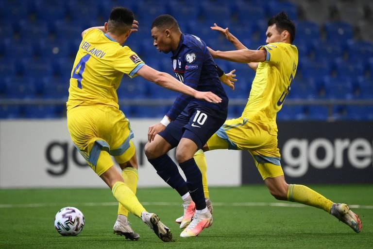 O atacante Kylian Mbappé (centro) disputa a bola com defensores do Cazaquistão em vitória da França nas eliminatórias para a Copa de 2022