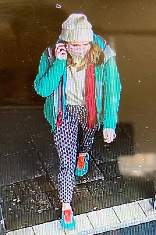 Moça de gorro, sapatilha verde, calça comprida e capa de chuva verde caminha, de máscara, falando ao telefone