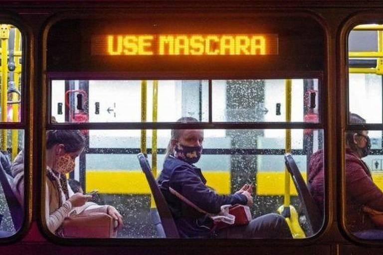 Pessoas sentadas em um ônibus; letreiro exibe a frase 'Use máscara'