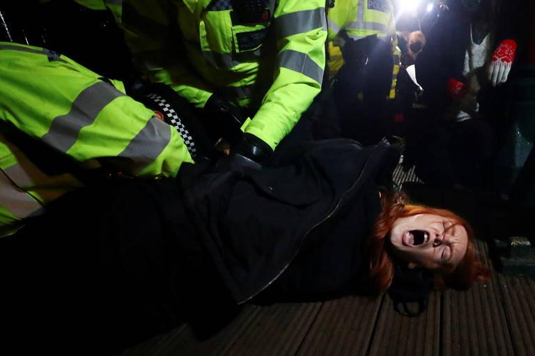 Mulher ruiva grita ao ser carregada por policiais dos quais só se vêem os braços