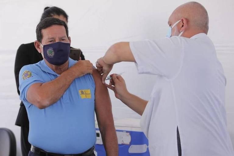 Vice-presidente Hamilton Mourão está de pé, com a manga da camiseta estendida, tomando a primeira dose da vacina contra Covid