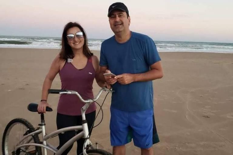 Daniela Arbex está ao lado do irmão em uma praia, com o mar ao fundo. Os dois estão de pé, e ela segura uma bicicleta. Ela está de calça justa escura e regata em tom avermelhado e óculos escuros. Ele está de bermuda e camiseta azuis e boné