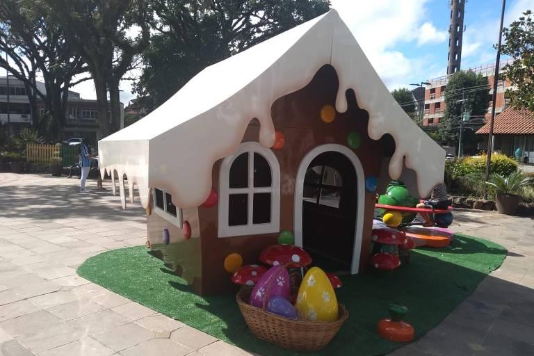Casinha no estilo casa de boneca com teto branco, como se fosse neve derretida, paredes marrons e grandes ovos de chocolate perto da porta