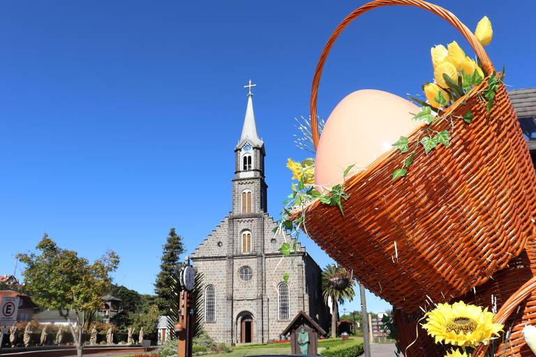 Igreja aparece no centro da foto, em segundo plano e, em primeiro plano, do lado direito, uma cesta com um ovo e flores. Ao fundo, céu azul
