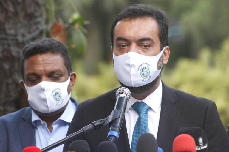 governador de máscara fala ao microfone