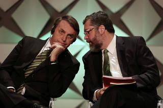 FILE PHOTO: Brazil's President Jair Bolsonaro talks to Minister of Foreign Affairs Ernesto Araujo during the Brazil Investment Forum in Sao Paulo