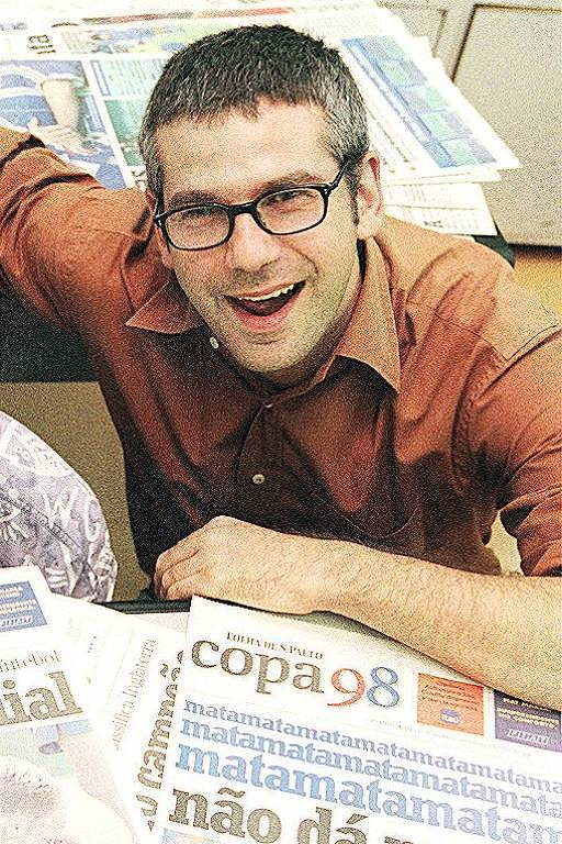 homem branco de cabelos pretos e curtos usa óculos e sorri para a foto