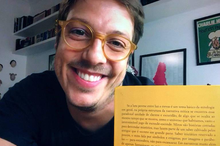 Fábio Porchat sorri e segura livro amarelo