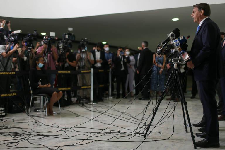 Observado por diversos fotógrafos, reporteres e cinegrafistas, o presidente Bolsonaro, fala á imprensa