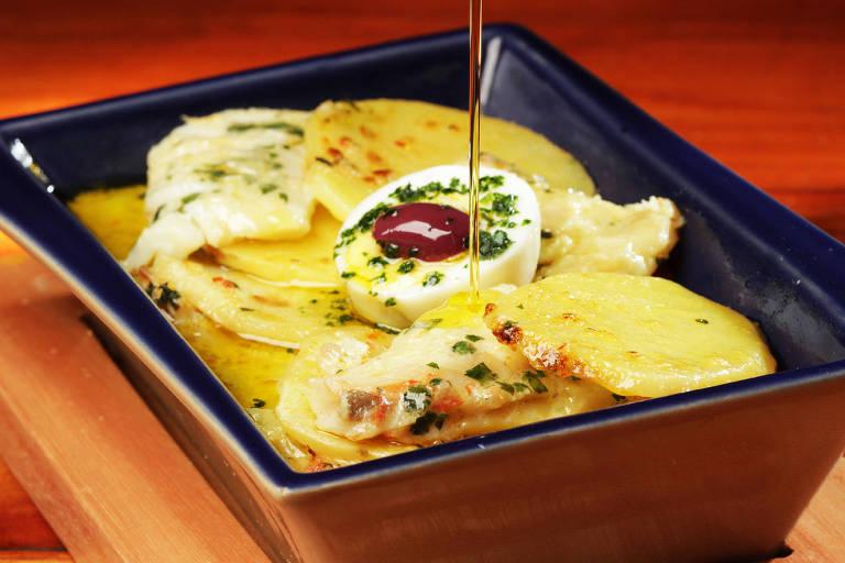 Em uma travessa, há uma receita de bacalhau. No meio, um ovo sendo regado por azeite