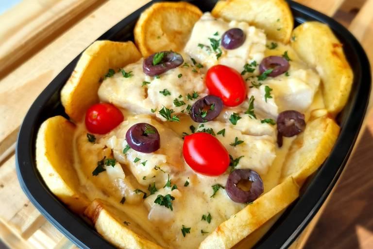 Em uma travessa, há uma receita de bacalhau com natas e batatas