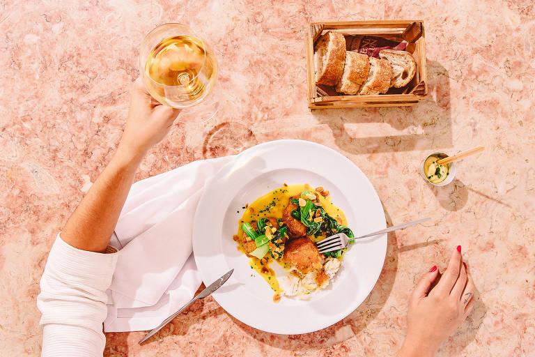 Uma mão segura uma taça de vinho. Sobre uma mesa, há um prato de bacalhau