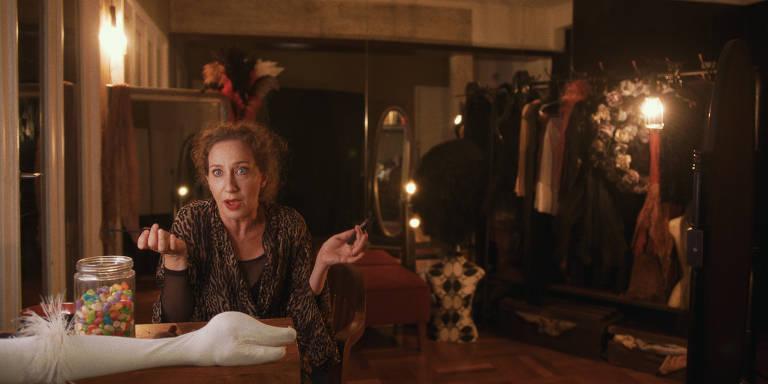 Em um camarim, atriz aparece do lado direito sentada em uma mesa falando com um cisne, feito pela mão de um ator, que está estirado na superfície