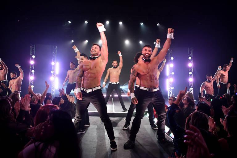homens tiram a roupa sobre palco iluminado