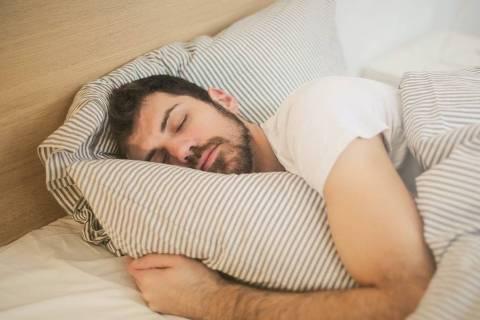 Homem dormindo abraçado a travesseiro
