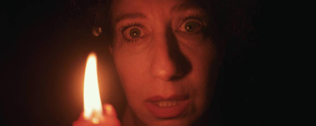 Rosto da atriz aparece em close, iluminado por uma vela em um ambiente escuro