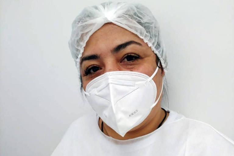 Semei Araujo Cunha está faz uma selfie. Ela está de touca, máscara e avental brancos