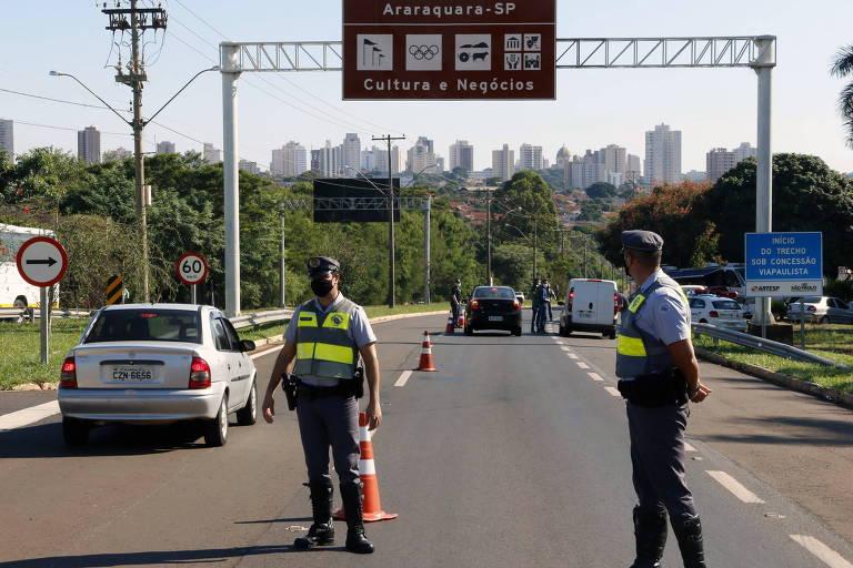 Imagem mostra dois policias fiscalizando via de acesso a Araraquara, com equipes ao fundo