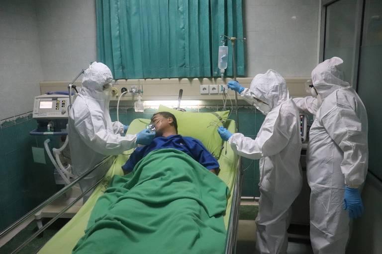 Homem entubado por três enfermeiros vestindo EPIs